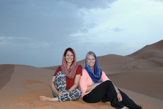 2 young women sitting in the sand at the Sahara Desert