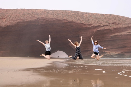 3 young women jumping at the beach
