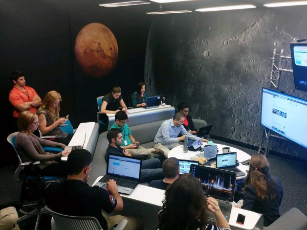 group of students with laptops listening to a presentation