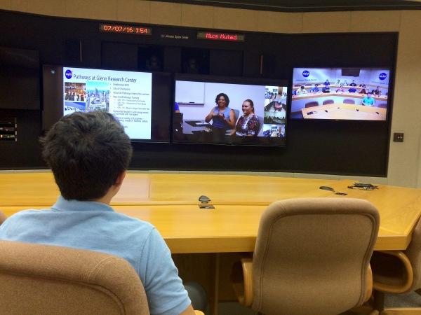 Person sitting at desk watching 3 computer monitors