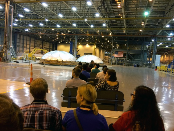 Group of people on motorized cart tour large warehouse building.