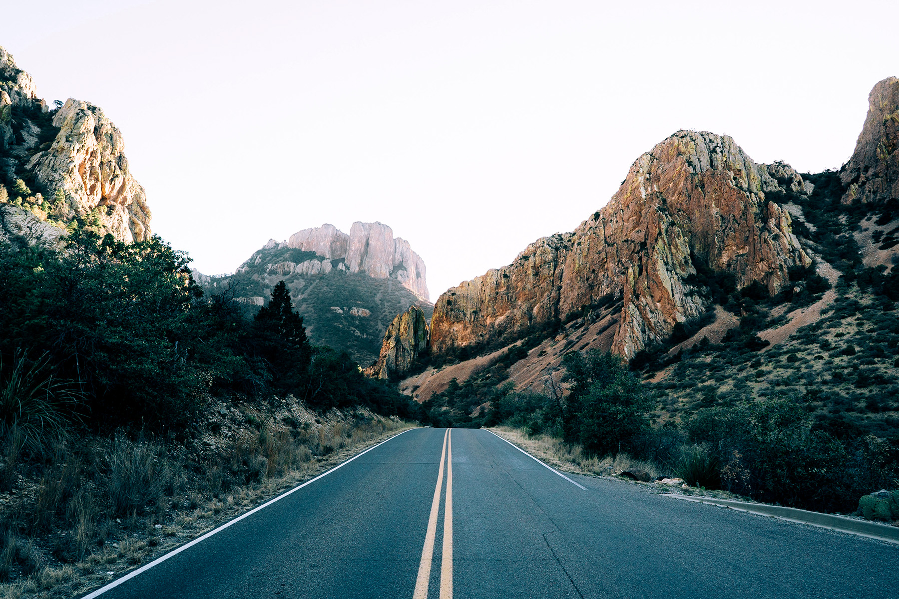 road with mountains surrounding it.