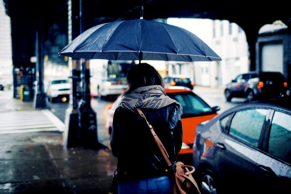 back of woman walking with umbrella on a rainy street