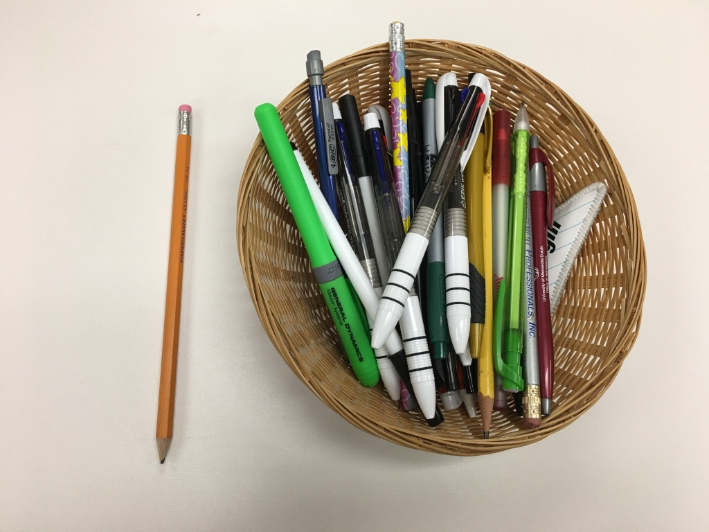 basket of pens and pencils with one pencil on table beside basket.