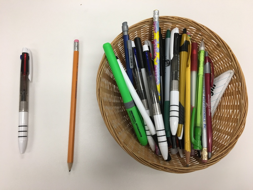 Basket of pens and pencils with a pen and pencil on table beside the basket.