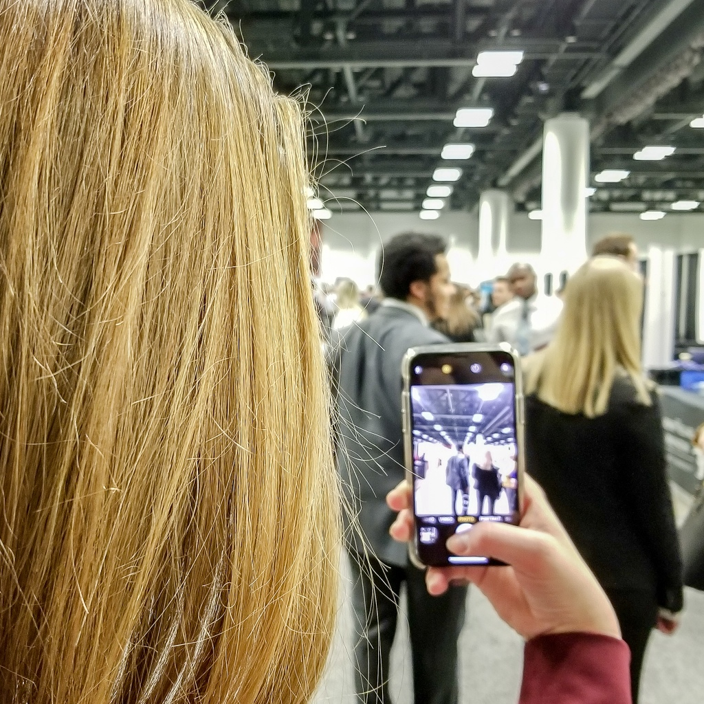 back of young woman's head and she's holding a phone. you see on the screen what she's taking a picture of.