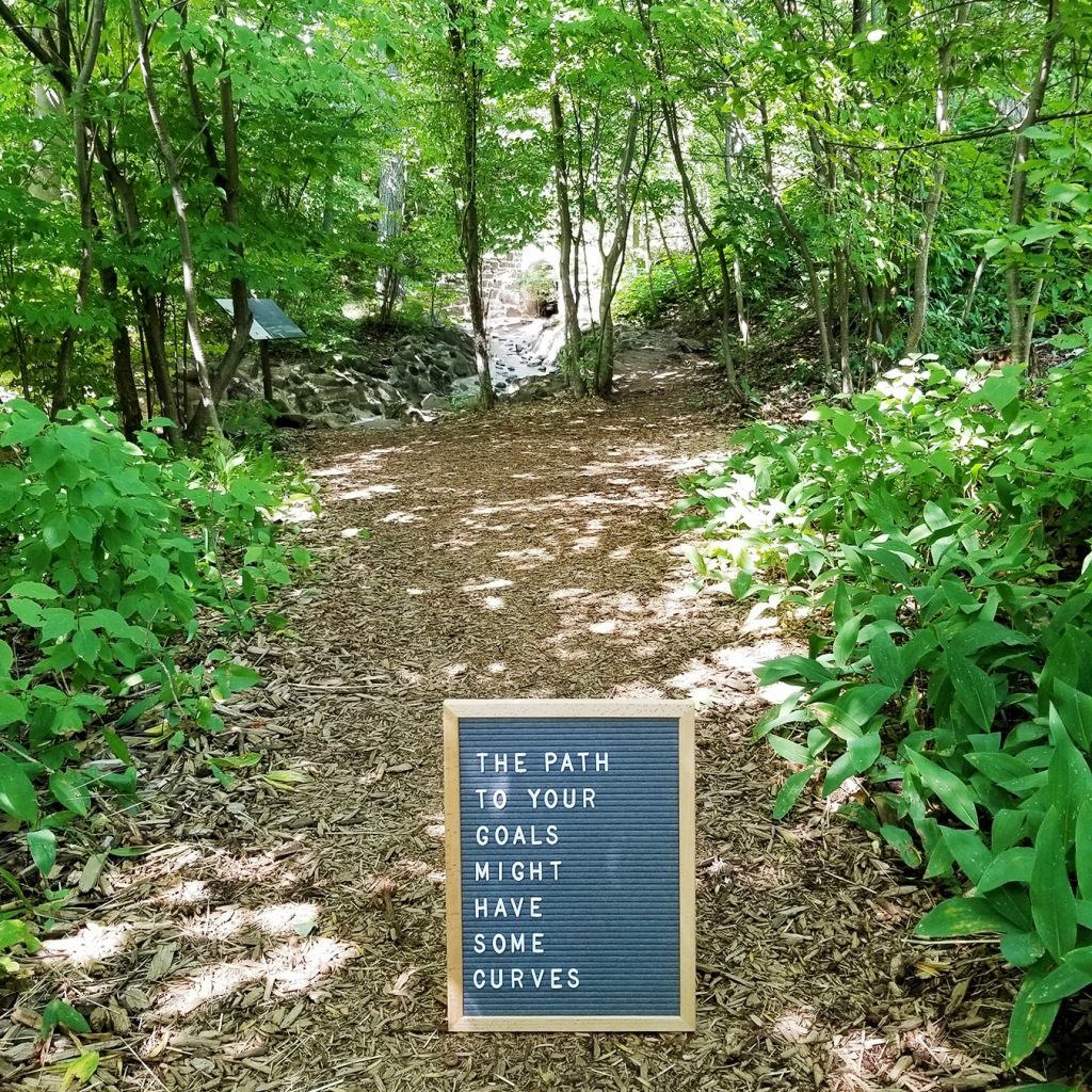 Image: nature trail in woods with letterboard on ground. Text on letterboard: The path to your goals might have some curves.