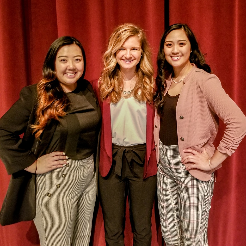 3 young women standing together at dress for success event.