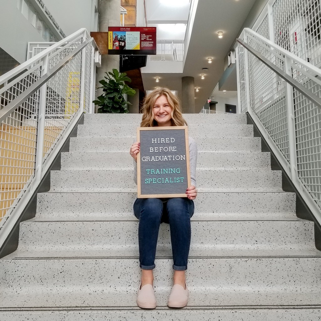 Rachel sitting on stairs in LSBE holding letterboard Text: Hired before graduation. Training Specialist.