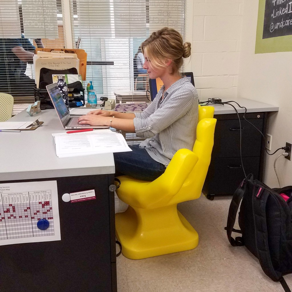 Rachel (in profile) sitting in yellow hand chair.