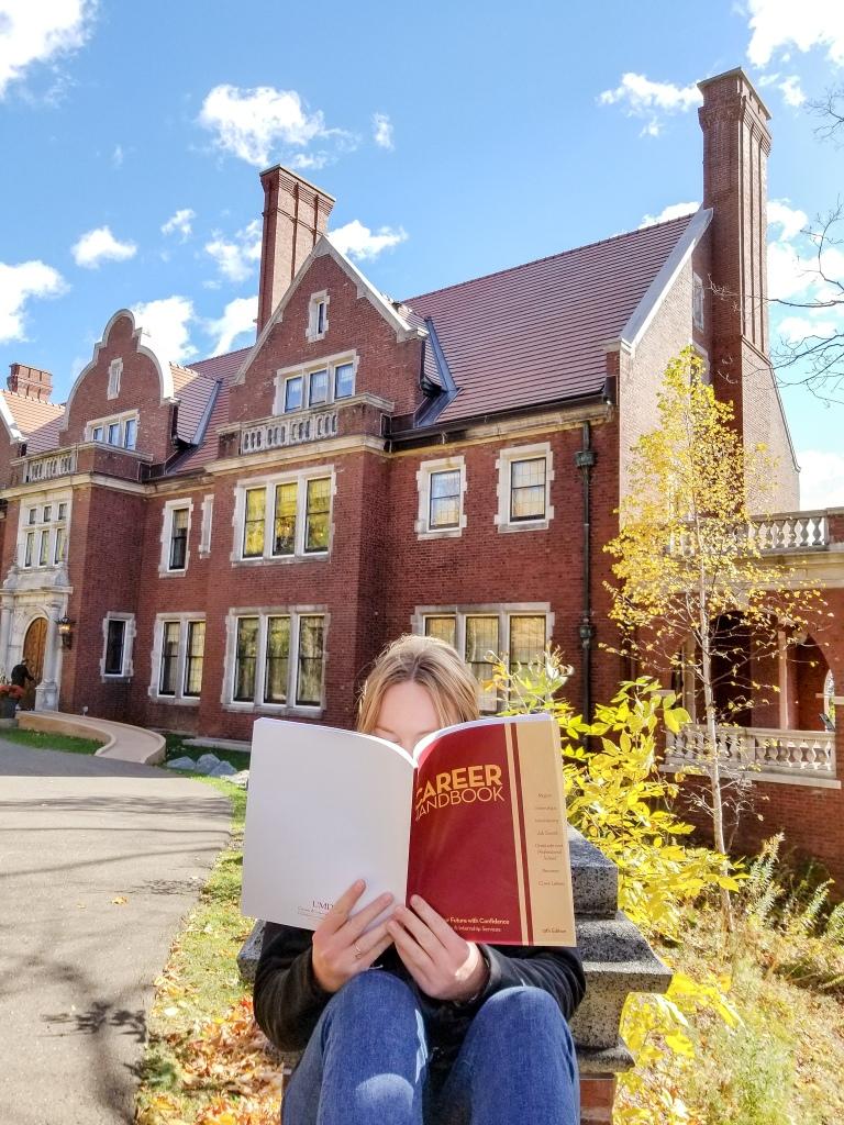 female college student holding Career Handbook with Glensheen Mansion in background