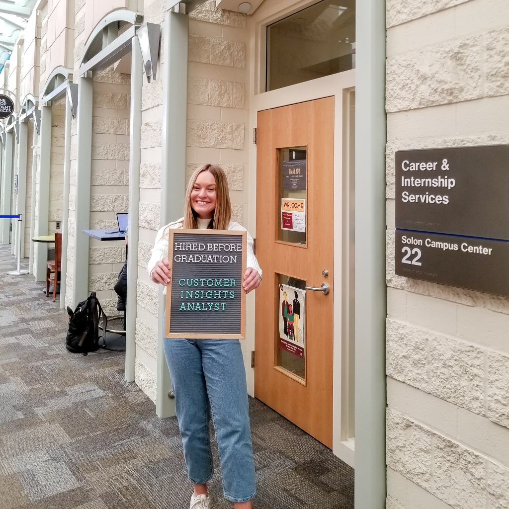 female college student standing in front of college campus office door holding letterboard. Letterboard text: Hired before graduation. Customer Insights Analyst.
