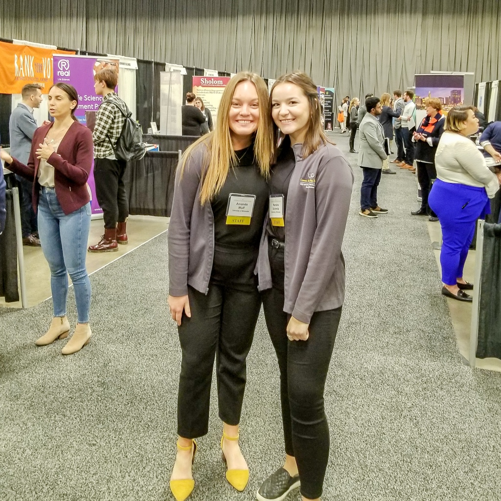 2 female college students standing next to each other at job & internship fair